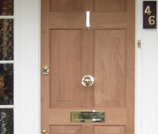 Using the existing old frame to match the original door, the new door was handmade using hardwood, and fitted with Yale locks.