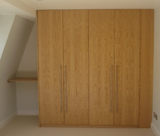 Made to measure floor to ceiling cupboard space made using oak veneer. Storage systems all built to your own requirements.