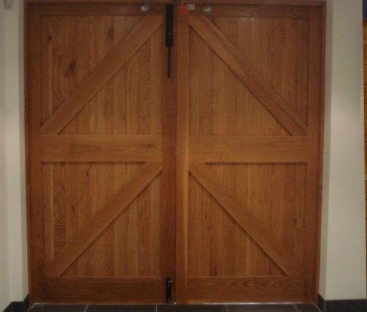 European oak garage doors which include a remote electrical opening system. The piece was spray finished in clear lacquer.
